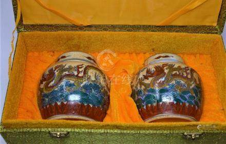 A pair of Chinese porcelain ginger jars and covers, with dragon decoration and set in presentation