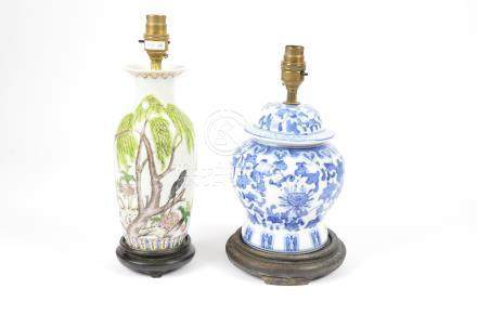 Two modern Chinese porcelain lamp bases, decorated with flowers, on wooden stands, no shades, 30