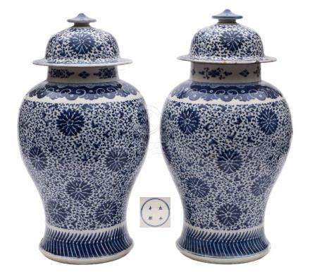 A pair of Chinese blue and white 'peony scroll' baluster jars and covers: painted overall with a