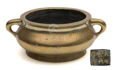 A Chinese cast bronze censer: of plain squat circular form with loop carrying handles to the sides,