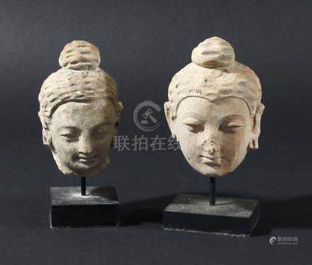 TWO CARVED STONE HEADS OF BUDDHA, 18th century or possibly earlier, Chinese or South East Asian,