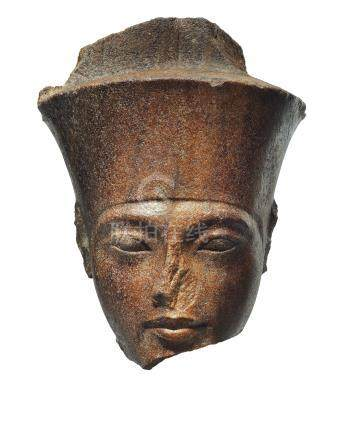 AN EGYPTIAN BROWN QUARTZITE HEAD OF THE GOD AMEN WITH THE FEATURES OF THE PHARAOH TUTANKHAMEN