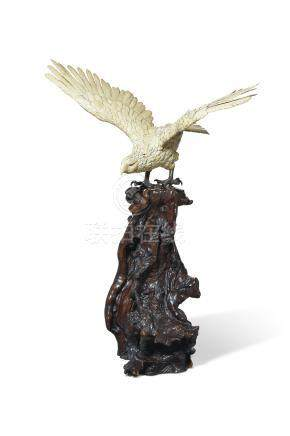 AN EXCEPTIONALLY LARGE JAPANESE CARVED IVORY AND PATINATED BRONZE EAGLE ON A ROOTWOOD BASE