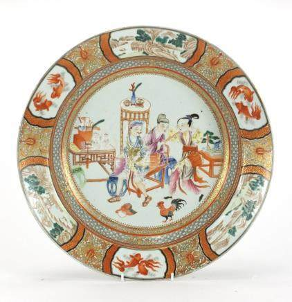 Chinese porcelain iron red shallow charger, finely hand painted in the famille rose palette with