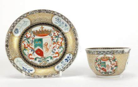 Chinese porcelain armorial tea bowl and saucer hand painted with crests and flowers, the tea bowl