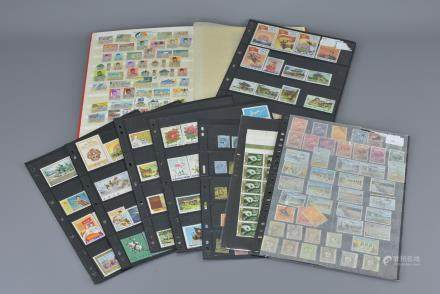 Stock book containing a quantity of Indonesian Stamps, mint and used plus a Page of Used George V Stamps, Page of Used Angola Stamps, Complete Sheet of 100 Spanish 70cts Stamps and Five Pages of Korean Stamps