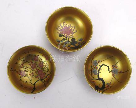 A set of three Japanese lacquered bowls, each internally gilt decorated with a blossoming shrub, d.