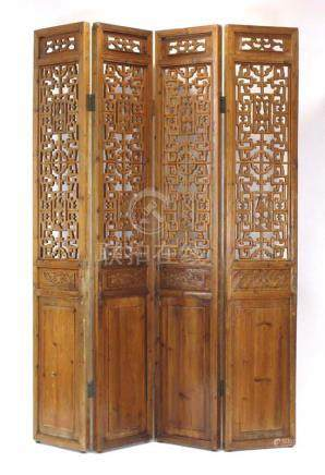 A late 19th century Chinese elm four section screen, typically carved with foliate motifs,