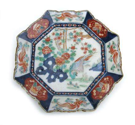 An Imari charger of octagonal form decorated with an exotic bird within a blossoming landscape, w.