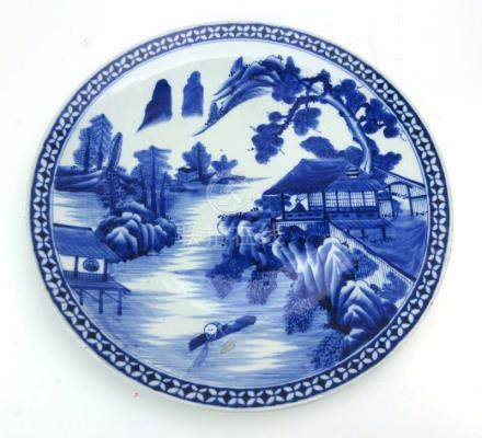 A large Japanese blue and white charger decorated with a village landscape,