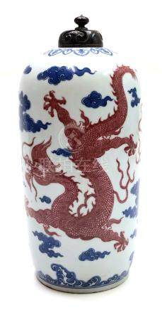 A Chinese porcelain vase and cover, Qianlong mark, with two red dragons amidst cloud scrolls,