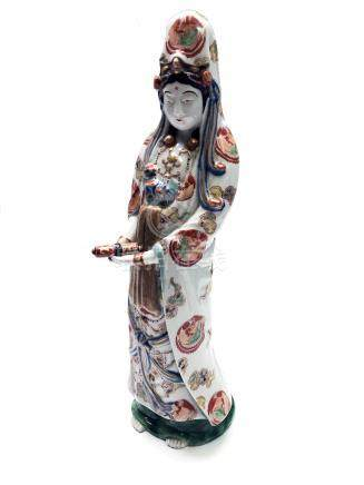 A Japanese porcelain figure of Guanyin, Meiji period, standing holding a scroll,