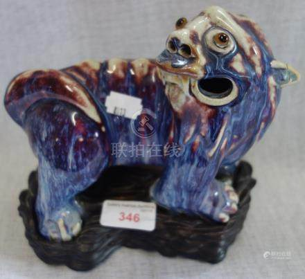 A CHINESE SHIWAN FLAMBE MYTHICAL BEAST, Quing, on a carved wooden base, 7.5cm long