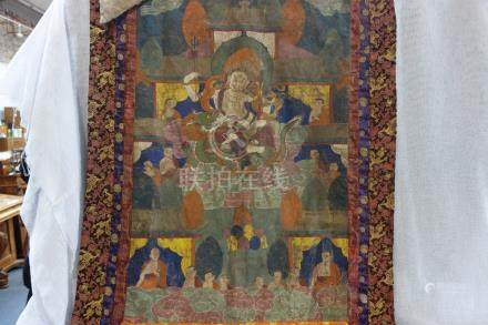 A SINO-TIBETAN THANGKA showing a central deity seated on a dragon and clouds surrounded by figures