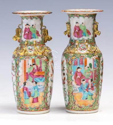 A pair of mid 19th Century Cantonese enamel twin handled baluster vases, decorated in the famille