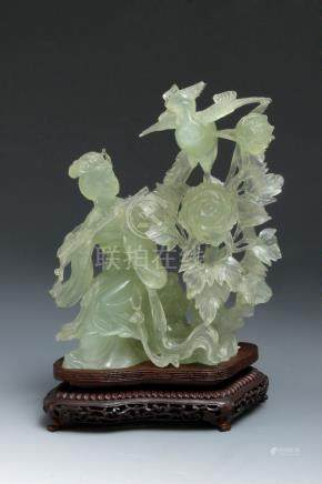A 20th century Chinese school. A carved jade figure of a Beauty with flowers