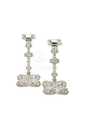 A matched pair of George III cast silver candlesticks