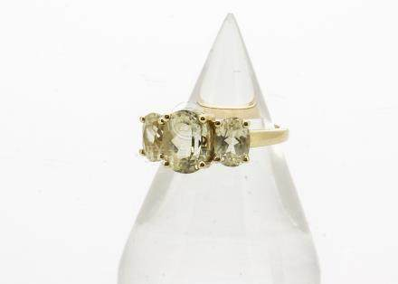 A 9ct gold three stone set spodumene dress ring, the three oval mixed cut stones in claw settings on