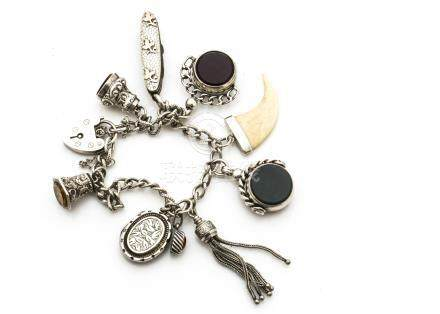 A silver curb linked charm bracelet, with padlock clasp, two swivel fobs, silver mounted manicure