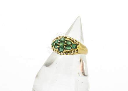 An 18ct gold emerald and diamond dress ring, the centre set with nine oval cut claw set emeralds