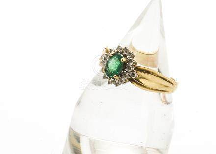 A 14ct gold emerald and diamond cluster ring, the oval cut central emerald claw set surrounded by