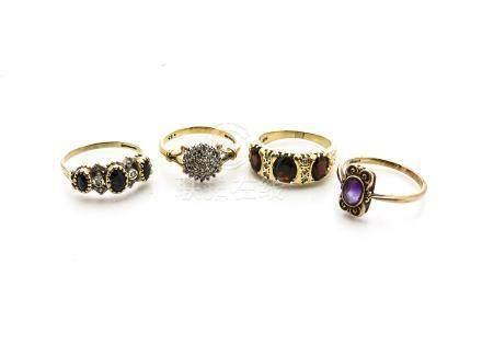 Four gem set gold dress rings, comprising an 18ct gold garnet and diamond three stone dress ring, an