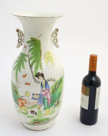 A 20thC Chinese twin handled baluster vase, decorated with figures in a garden with flying lanterns.