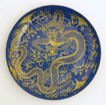 """A Chinese dish decorated with a gilt dragon on a blue ground. Approx. 10 1/4"""" diameter."""