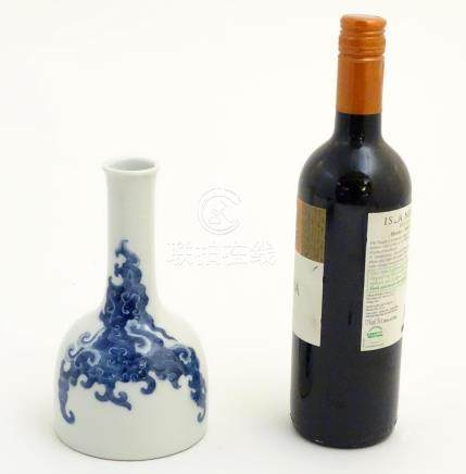 A Chinese blue and white bottle vase with a stylised, scrolling cloud pattern.