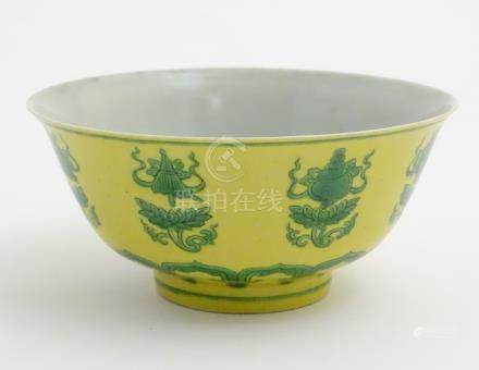 A Chinese bowl decorated with green auspicious motifs above scrolling lotus flowers on a yellow