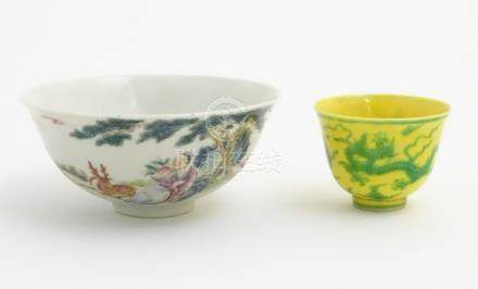 A Chinese famille rose bowl depicting figures and a deer in a landscape. Character marks to base.