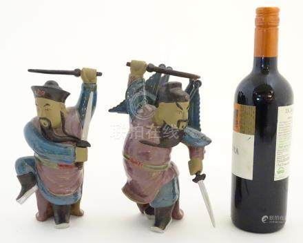 Two Oriental ceramic figures posed in combat with a lustre glaze, each holding two swords,