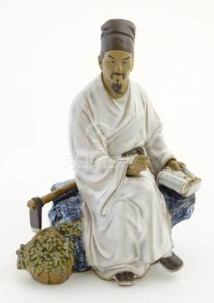 A Chinese partially glazed ceramic mudman figurine depicting a scholar/scribe,