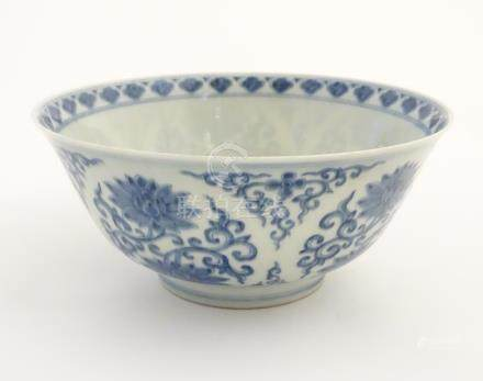 A Chinese blue and white bowl decorated with flowers and scrolling vines. Character marks to base.