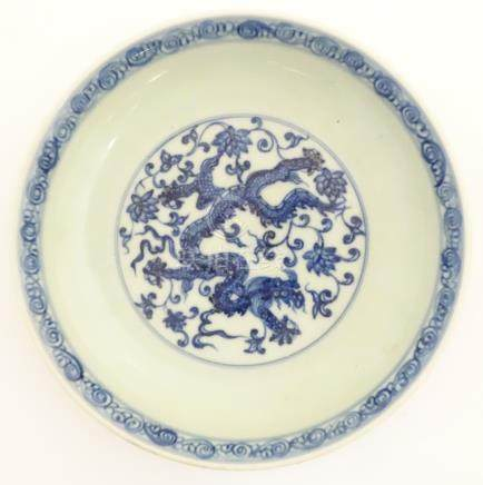 A Chinese blue and white dish decorated with dragons, and scrolling flowers.