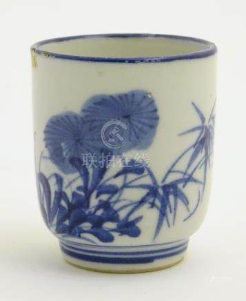 A Japanese blue and white pot with hand painted floral and foliate decoration.