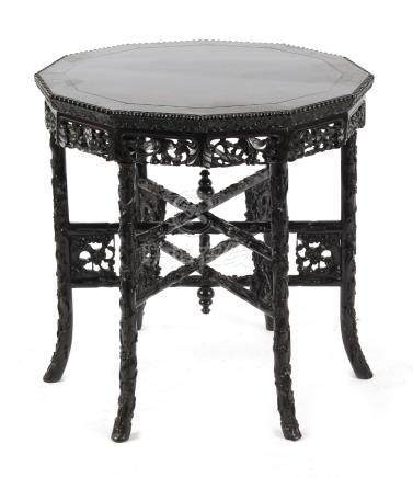 A late 19th / early 20th century Chinese carved hongmu dodecahedral table with folding six legged