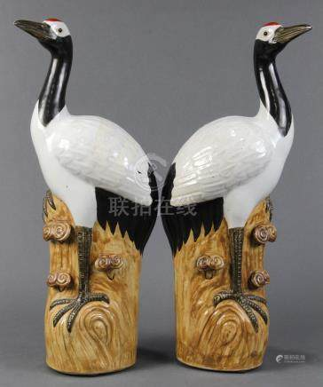 Pair of Chinese porcelain cranes, each standing on a rocky plinth accented by lingzhi, the base