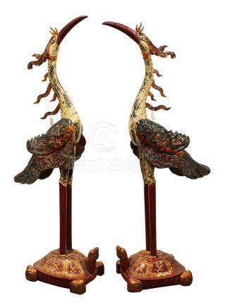 Pair of Vietnamese polychrome wood cranes, each with a white head and body accented by gilt wings,
