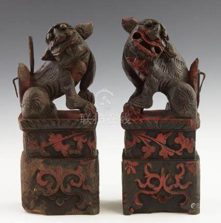 Pair of Chinese Ebonized Carved Wood Foo Lion Figures, late