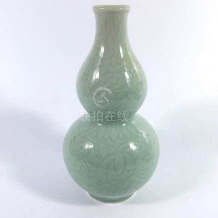 A Chinese celadon double gourd vase, relief moulded