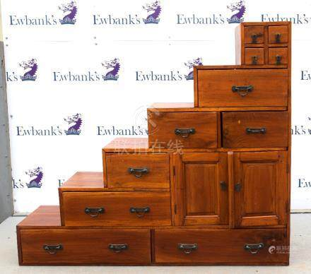 An Asian cabinet with six steps, designed after a Japanese Kaidan tansu original, with an