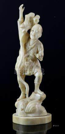 Late 19th/early 20th century Japanese carved ivory figure of a man with a long staff standing on a