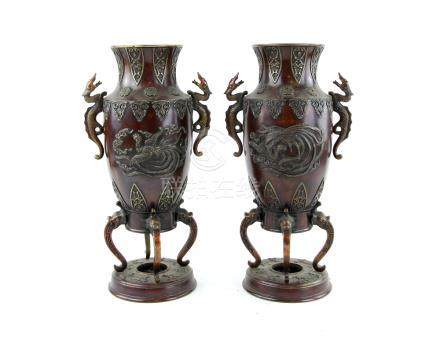 A pair of Japanese bronze vases; each one with trumpet neck and mythological animal handles,