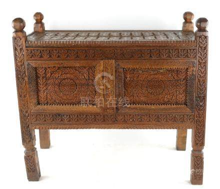 A small Indian hardwood Dowry Chest on shaped supports, carved with rows of stylised botanical or