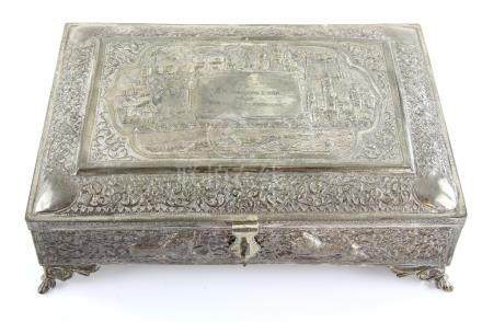 Indian white metal box with hinged cover embossed with a city and scrolling foliage decoration, on