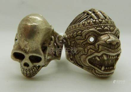 Two oriental style white metal rings, one in the form of a dragon mask, the other as a skull,