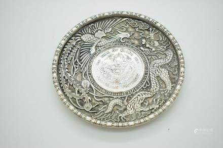 Chinese white metal pin dish with inset coin, further decorated with a dragon and a phoenix, 10cm