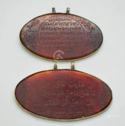 Two carnelian agate pendants with engraved script