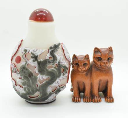 A Chinese glass overlaid scent bottle depicting a dragon and a boxwood netsuke depicting two cats,